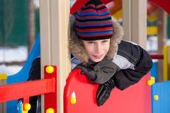 Niño feliz lindo que lleva la chaqueta caliente y un casquillo que juega en un patio Fotografía de archivo