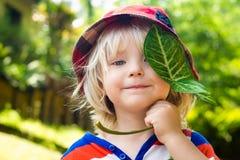 Niño feliz lindo que sostiene una hoja Imagen de archivo libre de regalías