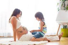 Niño feliz, muchacho, pintando en el vientre embarazada del ` s de la mamá Imagen de archivo libre de regalías