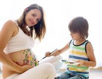 Niño feliz, muchacho, pintando en el vientre embarazada del ` s de la mamá Imagenes de archivo