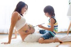 Niño feliz, muchacho, pintando en el vientre embarazada del ` s de la mamá Imágenes de archivo libres de regalías