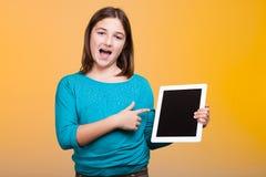 Niño feliz poiting en una tableta digital que ella está sosteniendo en ella Fotos de archivo