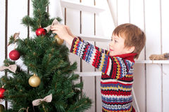 Niño feliz que adorna el árbol de navidad con las bolas. Foto de archivo libre de regalías