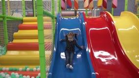 Niño feliz que baja diapositiva en el centro del juego de niños metrajes