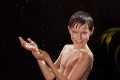 Niño feliz que camina debajo de la lluvia Imágenes de archivo libres de regalías