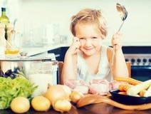 Niño feliz que cocina la sopa en casa foto de archivo libre de regalías