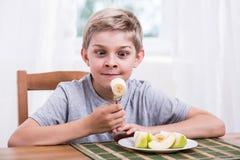 Niño feliz que come el plátano Imagenes de archivo