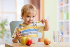 Niño feliz que come el queso de la comida con las frutas en casa Imágenes de archivo libres de regalías