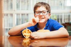 Niño feliz que come las patatas fritas Fotos de archivo libres de regalías
