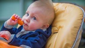 Niño feliz que come un signo de intercalación metrajes