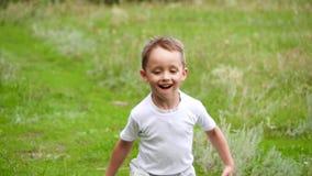 Niño feliz que corre en hierba verde en la cámara lenta almacen de video