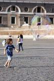 Niño feliz que corre hacia una burbuja de jabón Imagen de archivo