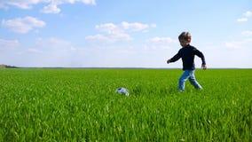 Niño feliz que corre a través de un campo de la hierba verde y que golpea un balón de fútbol con el pie en la cámara lenta metrajes