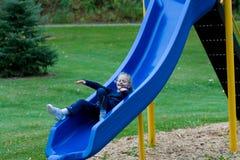 Niño feliz que desliza abajo una diapositiva. Imagen de archivo