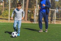 Niño feliz que golpea la bola con el pie con alegría Fotografía de archivo libre de regalías