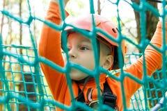 Niño feliz que goza en un parque de la aventura que sube Imagen de archivo