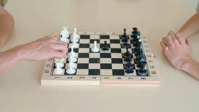 Niño feliz que juega a ajedrez con un hombre mayor en casa almacen de video