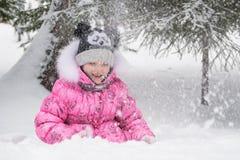 Niño feliz que juega al aire libre divertirse de la nieve que cae en los wi Foto de archivo libre de regalías