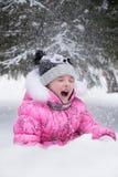 Niño feliz que juega al aire libre divertirse de la nieve que cae en los wi Imagen de archivo
