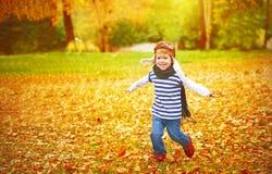 Niño feliz que juega al aviador experimental al aire libre en otoño Foto de archivo