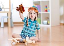 Niño feliz que juega con el aeroplano del juguete en casa imagenes de archivo
