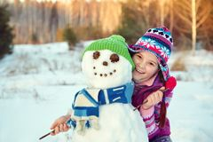 Niño feliz que juega con el muñeco de nieve Foto de archivo libre de regalías