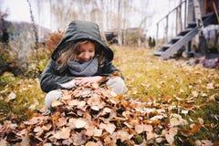 Niño feliz que juega con las hojas en otoño Actividades al aire libre estacionales con los niños Imagen de archivo libre de regalías