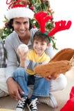 Niño feliz que juega con un regalo de la Navidad Fotos de archivo