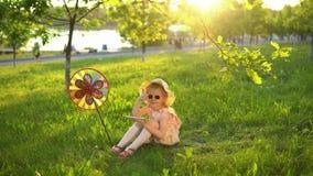 Niño feliz que juega en hierba debajo de robles jovenes en un parque público en la puesta del sol almacen de metraje de vídeo