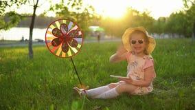 Niño feliz que juega en hierba debajo de robles jovenes en un parque público en la puesta del sol almacen de video
