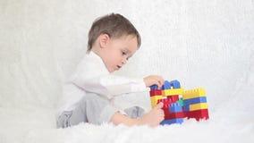 Niño feliz que juega en los bloques coloreados en el sofá almacen de video