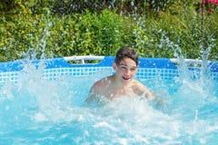 Niño feliz que juega en una piscina al aire libre Imagenes de archivo