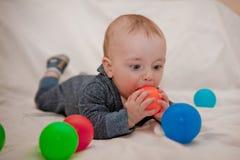 Niño feliz que juega y que se divierte con las bolas coloridas Imagenes de archivo