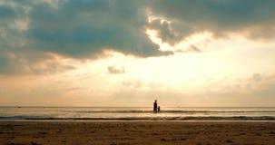 Niño feliz que lleva a cabo la mano de su padre Walking Near el mar Paseo de la familia en fondo del cielo de la puesta del sol S almacen de video