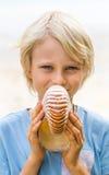 Niño feliz que lleva a cabo una cáscara del nautilus fotos de archivo