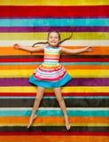Niño feliz que miente en el fondo de la alfombra del color Imágenes de archivo libres de regalías