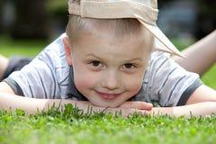 Niño feliz que miente en la hierba Foto de archivo libre de regalías