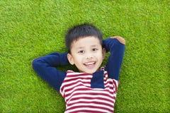 Niño feliz que miente y que lleva a cabo su cabeza Fotos de archivo