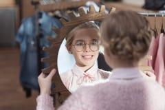 niño feliz que mira el espejo en sus manos la tienda fotografía de archivo