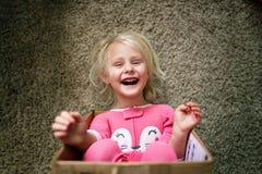 Niño feliz que ríe como ella juega en caja de cartón en su hogar fotografía de archivo