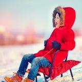 Niño feliz que resbala abajo de la colina en día de invierno hermoso Fotos de archivo