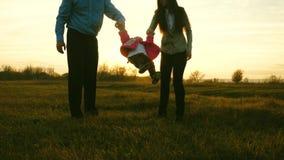 Niño feliz que salta en el parque con el papá y la mamá Juego de la mamá y del papá con el bebé los padres aumentan las manos del almacen de video