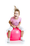Niño feliz que salta en la bola que despide aislada Fotografía de archivo