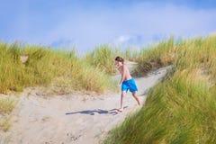 Niño feliz que salta en las dunas Imagenes de archivo