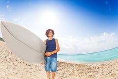 Niño feliz que se coloca en la playa arenosa con el tablero de resaca Fotografía de archivo
