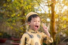Niño feliz que se divierte con el vestido tradicional ao dai en Ochna adentro Fotos de archivo