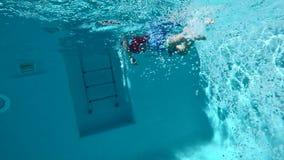 Niño feliz que se divierte en piscina clara azul almacen de metraje de vídeo
