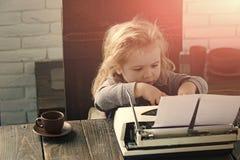 Niño feliz que se divierte pequeño muchacho o niño del hombre de negocios con la máquina de escribir fotografía de archivo