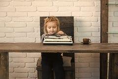 Niño feliz que se divierte pequeño muchacho o niño sonriente del hombre de negocios con la máquina de escribir foto de archivo