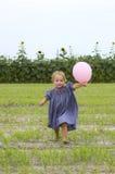 Niño feliz que se ejecuta con el globo foto de archivo